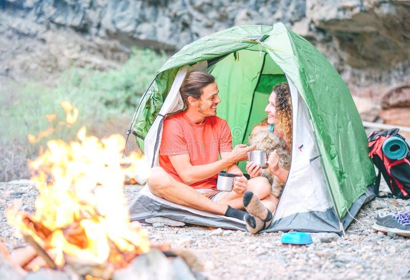 Счастливые пары hikers с их собакой располагаясь лагерем с шатром вокруг гор утеса рядом с огнем - людьми ослабляя в лагере стоковые фото