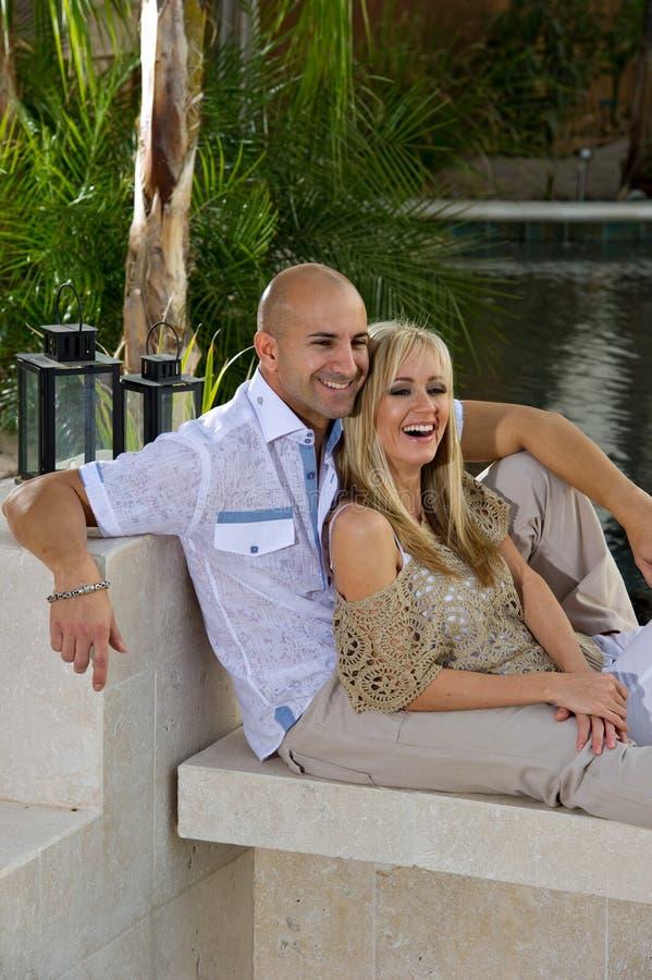 Счастливые пары lounging бассеином стоковые изображения rf