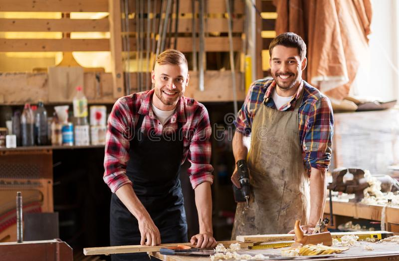 Счастливые плотники со сверлом и доска на мастерской стоковые изображения