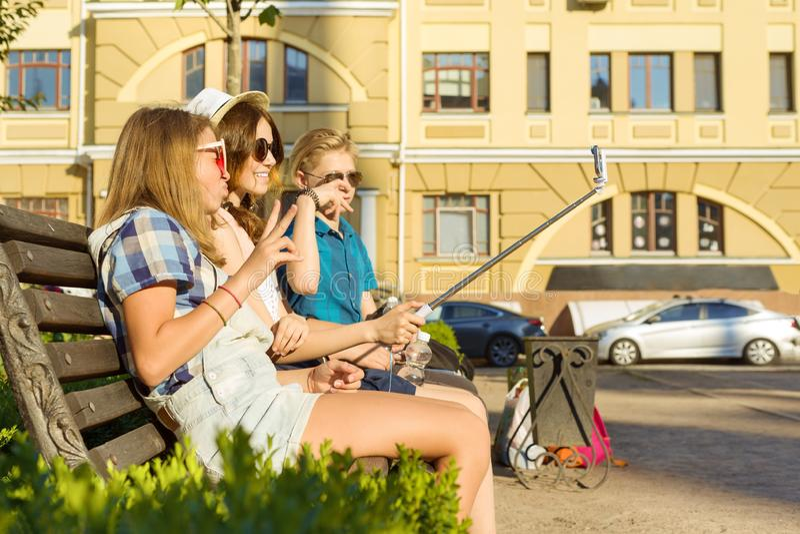 Счастливые 4 подростковых друзья или студента средней школы имеют потеху, говорящ, читающ телефон, делая фото selfie в городе на  стоковые изображения rf