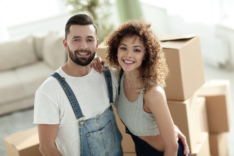 Счастливые пожененные пары на предпосылке новой квартиры стоковые фотографии rf