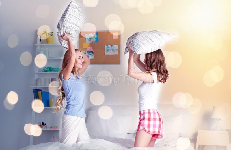 Счастливые предназначенные для подростков подруги воюя подушки дома стоковая фотография rf