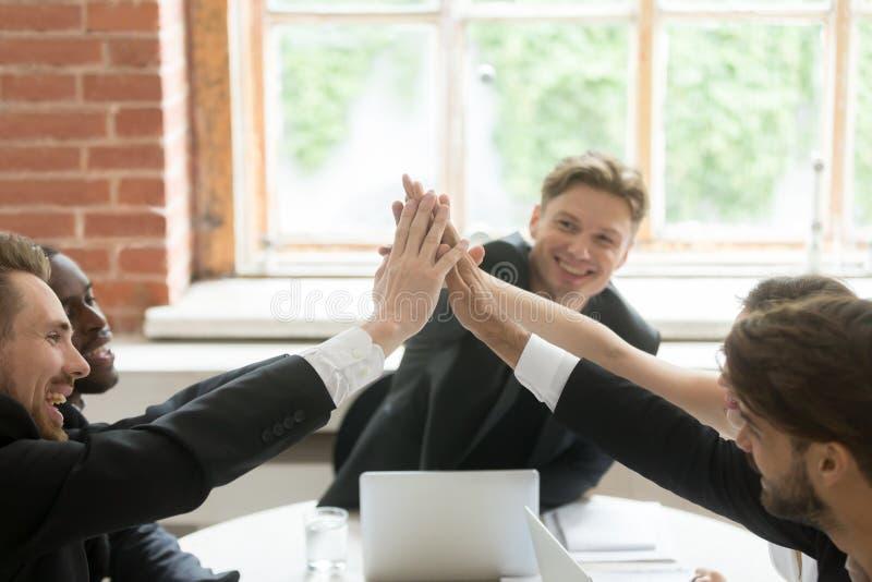 Счастливые предприниматели давая максимум 5 на встрече, празднуя бушель стоковые изображения