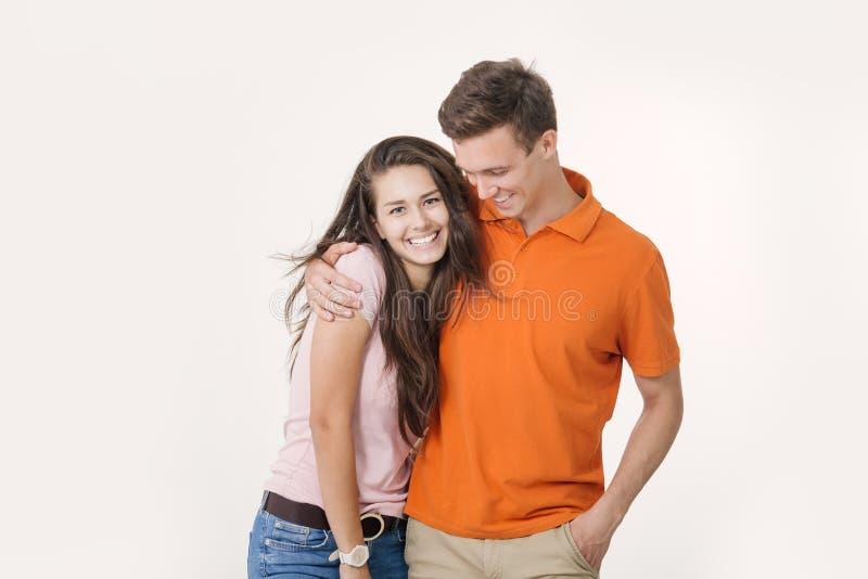 Счастливые прекрасные пары обнимая и усмехаясь смотрящ камеру на белой предпосылке стоковое изображение rf