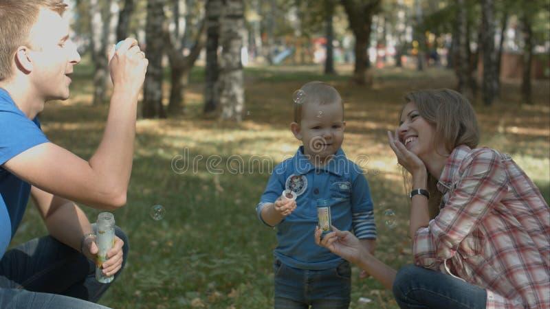 Счастливые пузыри матери, отца и сына дуя в парке стоковые изображения