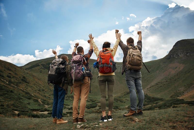 Счастливые путешественники кладя руки вверх после достижения верхней части стоковая фотография