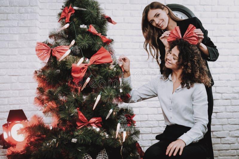 Счастливые работники украшая рождественскую елку в офисе стоковые изображения