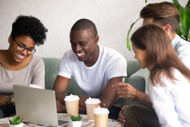 Счастливые разнообразные друзья смеются висеть вне в кафе стоковая фотография rf