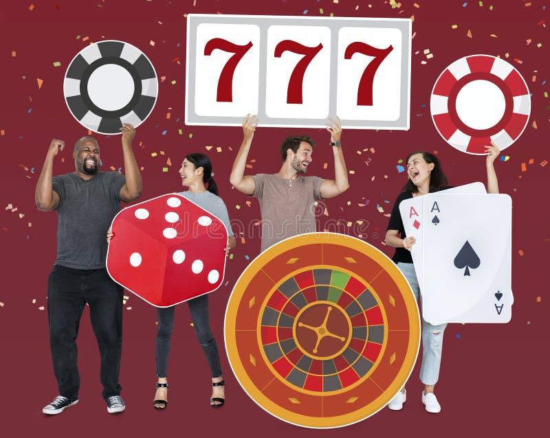 Счастливые разнообразные люди держа значки казино стоковые изображения
