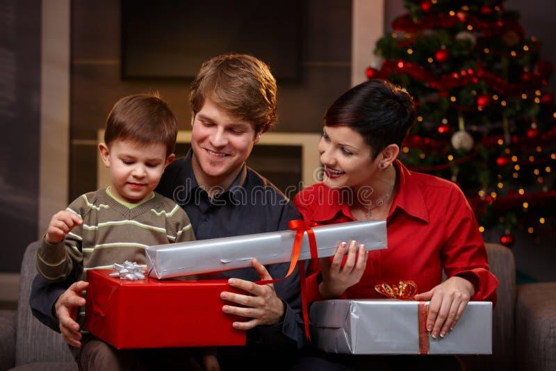 Счастливые родители давая подарки рождества к сынку стоковое фото rf