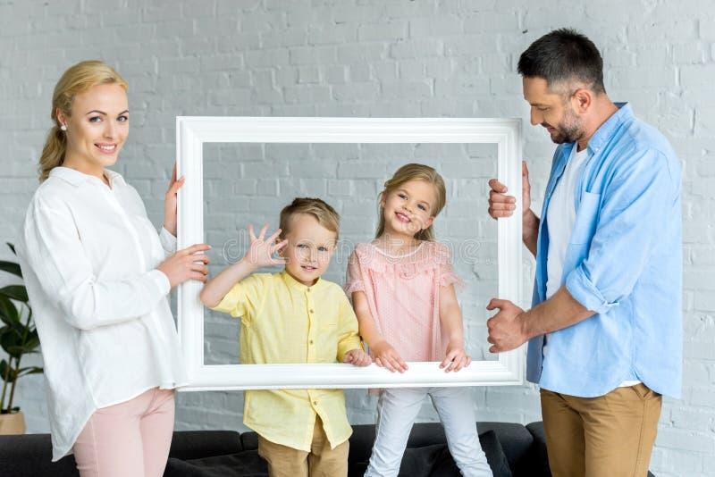 счастливые родители держа рамку и милый усмехаться маленьких ребят стоковое фото rf