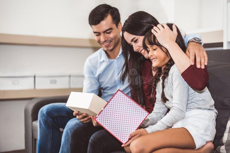 Счастливые родители и маленькая девочка семьи смотря в подарочную коробку в рождестве и Новом годе на софе в живя комнате Xmas пр стоковое изображение