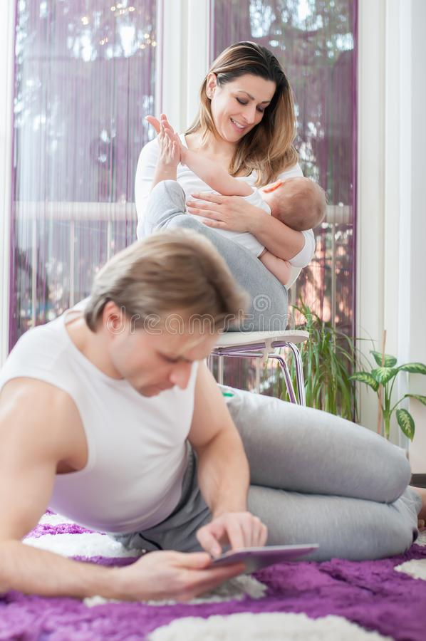счастливые родители Отец кладя вниз на пол и играя на планшете Мать кормит ее ребенка грудью стоковые изображения