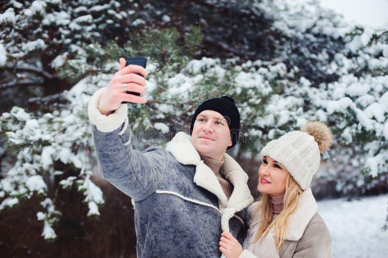 счастливые романтичные пары делая selfie внешний в снежной зиме стоковое изображение rf