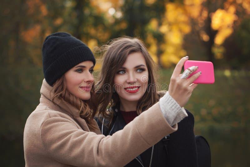 Счастливые самые лучшие подруги делая selfie на smartphone стоковое фото