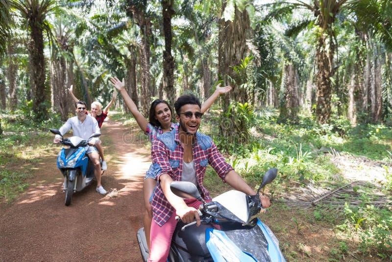 Счастливые свободные пары управляя самокатом наслаждаются перемещением в поездке друзей тропического леса жизнерадостной стоковое изображение rf