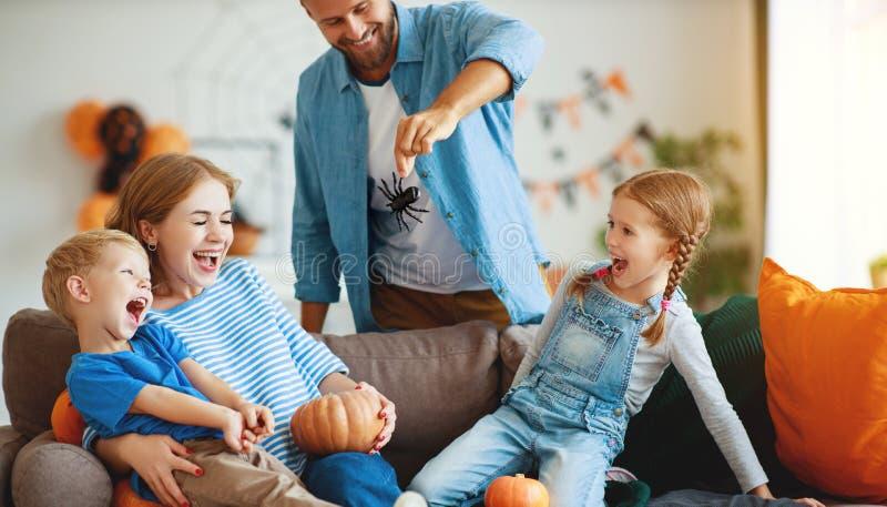 Счастливые семьи отец и дети готовятся к Хэллоуин украшать дом с тыквами и смеются, играют и пугаются стоковые изображения rf