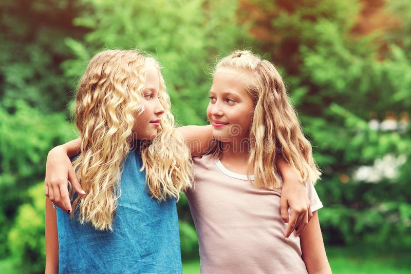 Счастливые сестры близнецов обнимаются на улице. Семейные прогулки в л стоковое фото rf