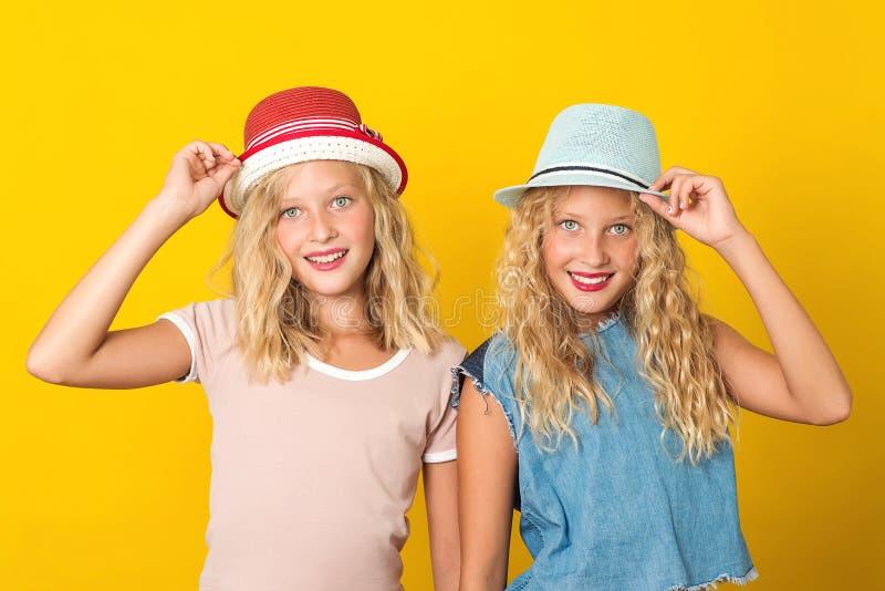 Счастливые сестры-близнецы в летних шляпах, на желтом фоне. Летняя мода стоковые изображения