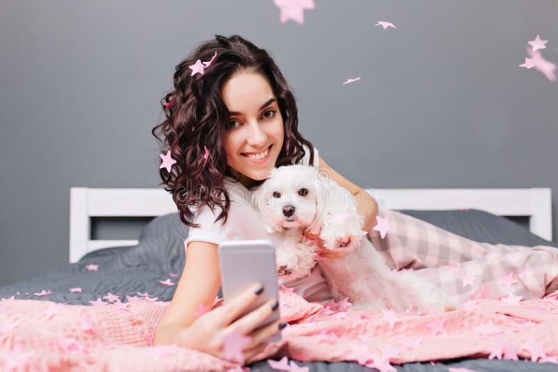 Счастливые сладкие моменты молодой красивой женщины в пижамах с отрезанным вьющиеся волосы брюнета делая фото selfie с собакой вн стоковые фото