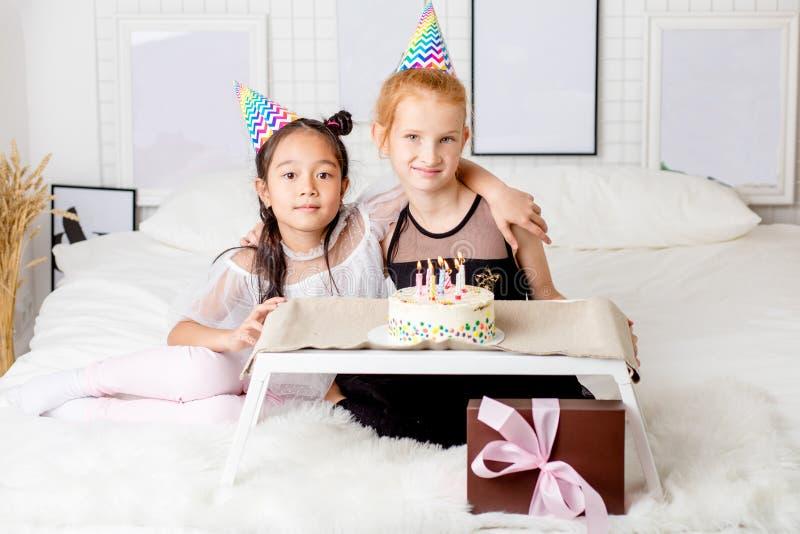 Счастливые смешанные, который участвуют в гонке дети сидя на кровати и представляя к камере стоковые фотографии rf