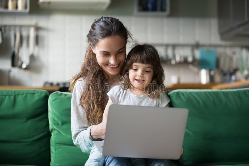 Счастливые смеясь мать и дочь используя ноутбук стоковые фото