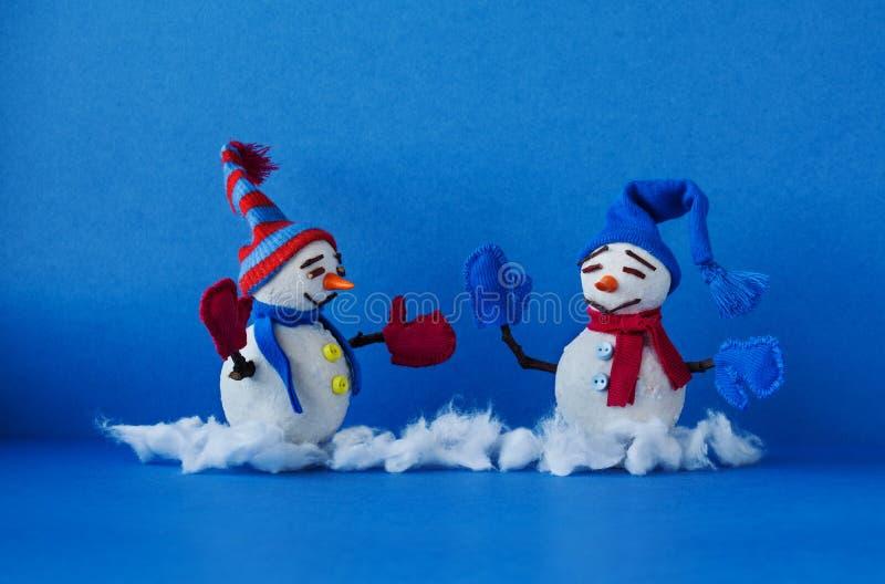 Счастливые снеговики на голубой предпосылке Характеры снеговика зимы традиционные с mittens шарфа и смешными шляпами Новый Год Xm стоковые фотографии rf