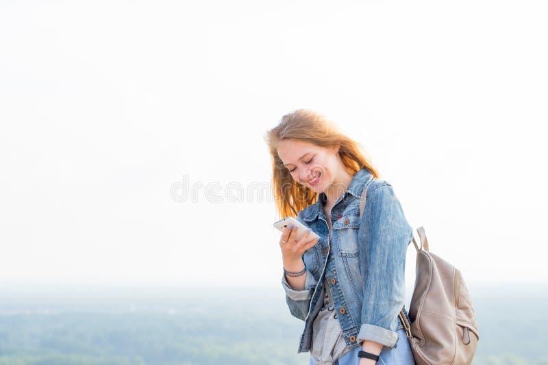 Счастливые сообщения чтения молодой женщины, наблюдая что-то на интернете через smartphone и усмехаясь в природе стоковое изображение rf