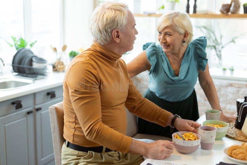 Счастливые соперничанные испуская лучи славн-апеллируя привлекательные пожилые супруги говоря во время завтрака стоковые фото