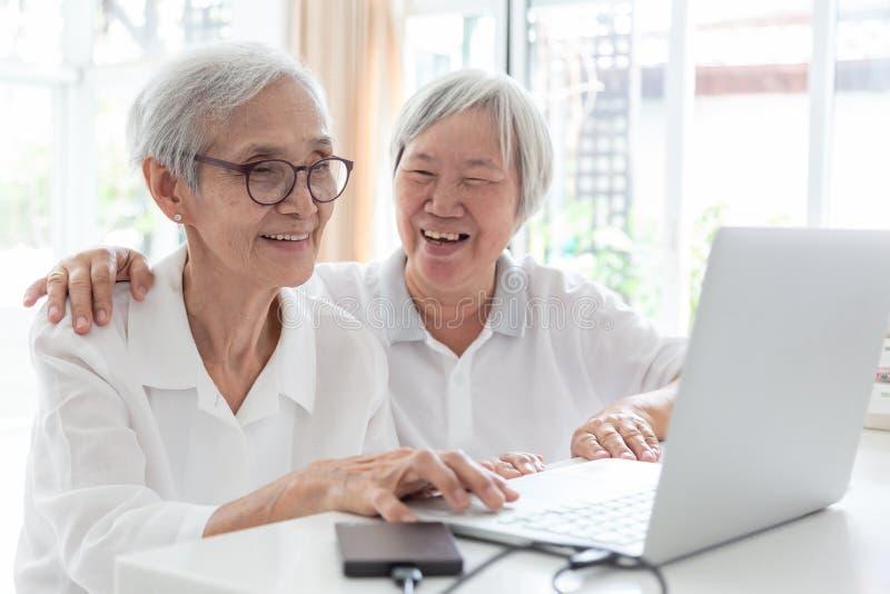 Счастливые 2 старшие азиатские женщина, сестры или друзья говоря и наслаждаясь использующ ноутбук совместно дома, усмехаться прес стоковые изображения rf