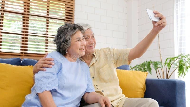 Счастливые старшие азиатские пары принимая комнату selfie дома живущую, активные старшие людей в счастливом моменте, случайные лю стоковая фотография rf