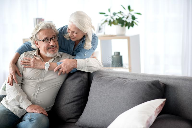 Счастливые старшие любящие пары отдыхая в живущей комнате стоковые изображения