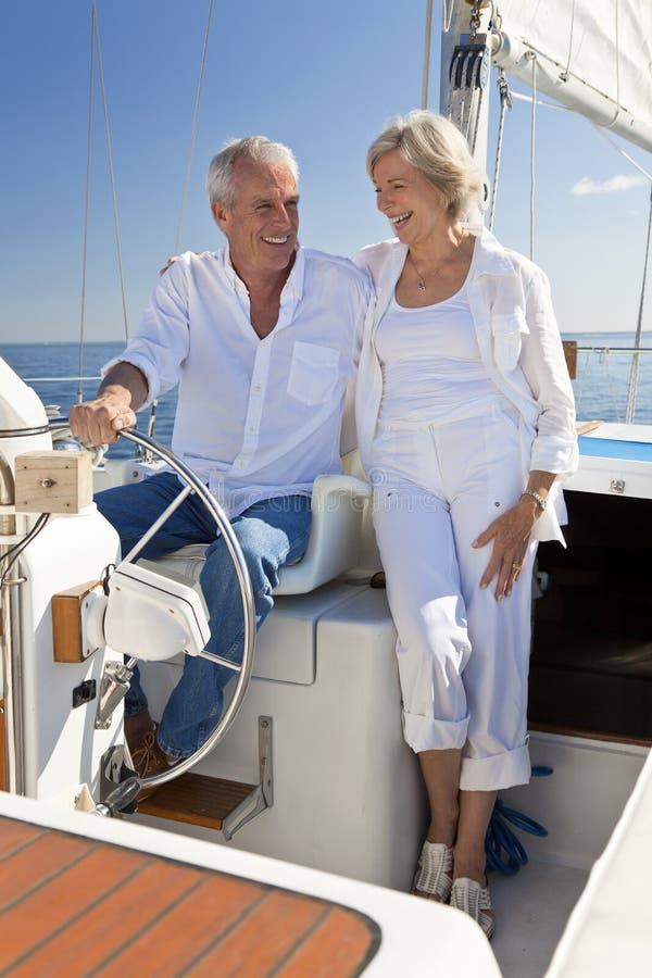 Счастливые старшие пары на колесе шлюпки ветрила стоковые фотографии rf