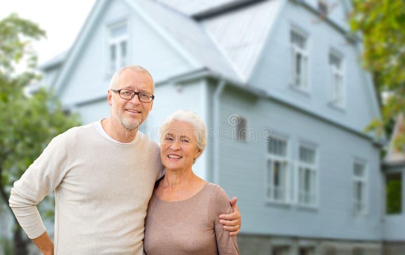 Счастливые старшие пары обнимая над предпосылкой дома стоковое изображение