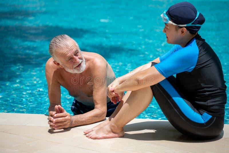 Счастливые старшие пары ослабляя в бассейне совместно t выход на пенсию, разминка, фитнес, спорт, тренировка стоковое фото rf