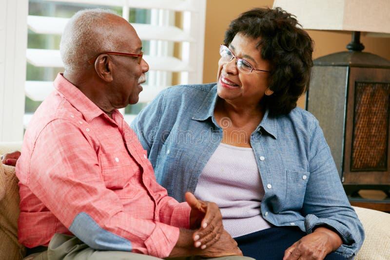 Счастливые старшие пары сидя на софе на дому стоковое фото rf