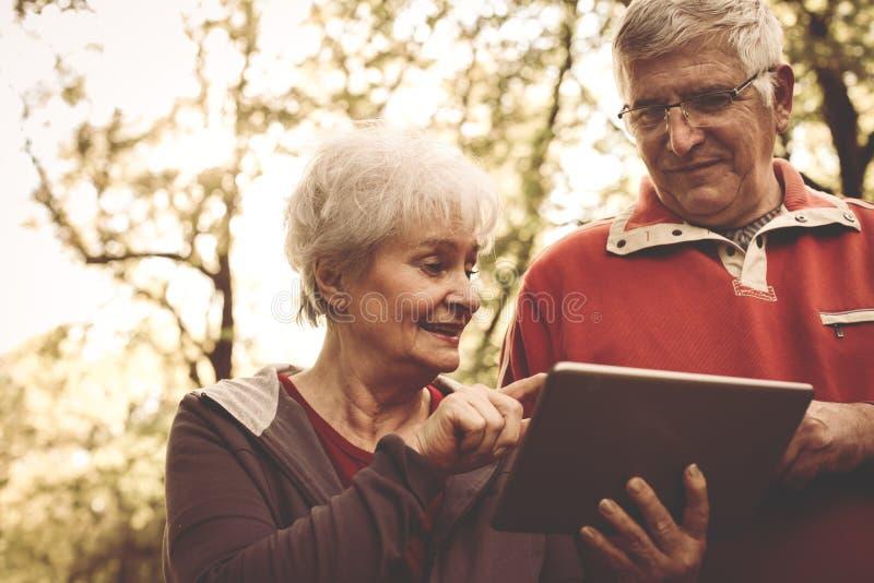 Счастливые старшие пары стоя в парке и используя iPod стоковые фотографии rf