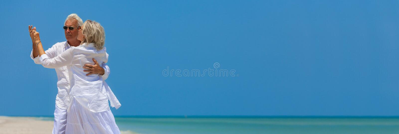 Счастливые старшие танцы пар держа руки на тропическом пляже стоковая фотография