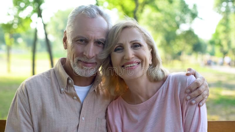Счастливые старые пары обнимая и смотря камеру, образ жизни выхода на пенсию, дедов стоковые изображения rf