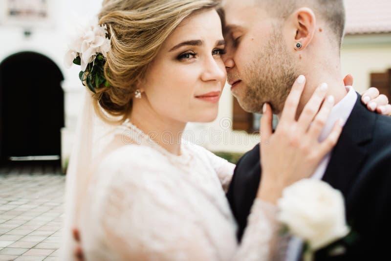 Счастливые стильные пары outdoors целовать groom невесты стоковая фотография rf