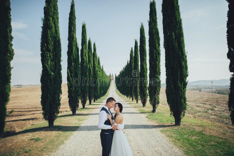 Счастливые стильные усмехаясь пары идя в Тоскану, Италию на их стоковые изображения