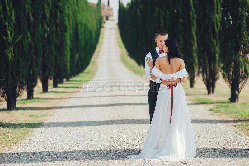 Счастливые стильные усмехаясь пары идя и целуя в Тоскане, Ita стоковое фото rf