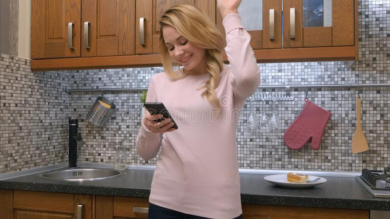 Счастливые танцы молодой женщины в кухне слушая к музыке на smartphone дома стоковые фото