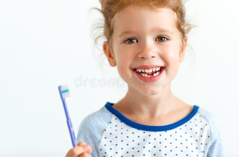 Счастливые улыбки девушки ребенка с зубной щеткой стоковое фото