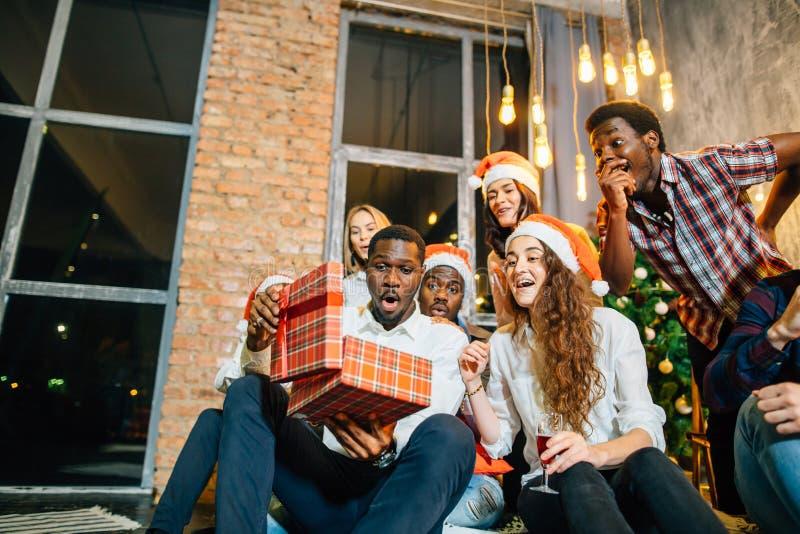 Счастливые усмехаясь друзья раскрывая волшебный подарок рождества стоковое изображение rf
