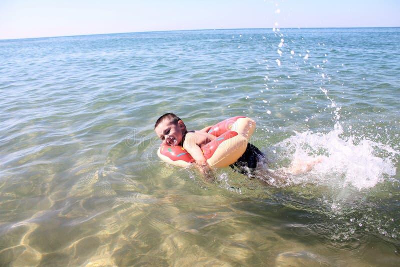 Счастливые усмехаясь заплывы ребенка в море стоковые фотографии rf