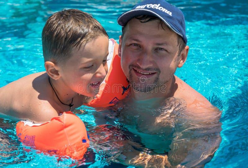 Счастливые усмехаясь отец и сын на празднике в бассейне стоковая фотография rf