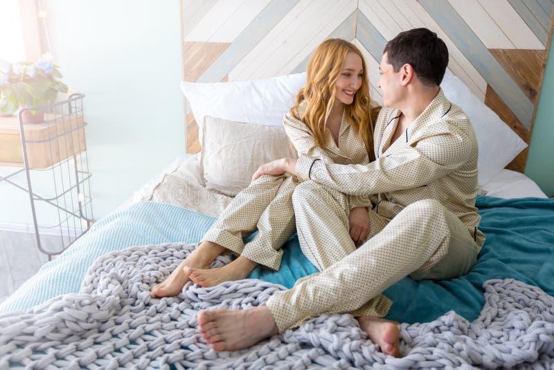 Счастливые усмехаясь пары лежа в кровати дома стоковые изображения rf