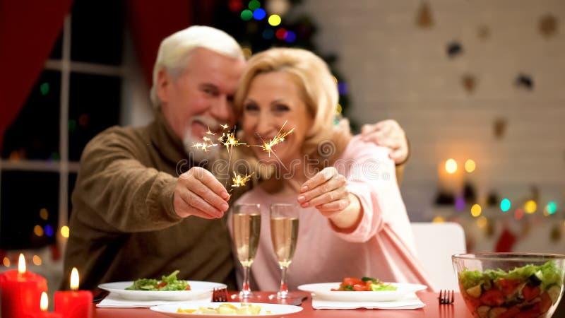 Счастливые усмехаясь пожилые пары празднуя Xmas, держащ света Бенгалии и усмехаться стоковое изображение rf