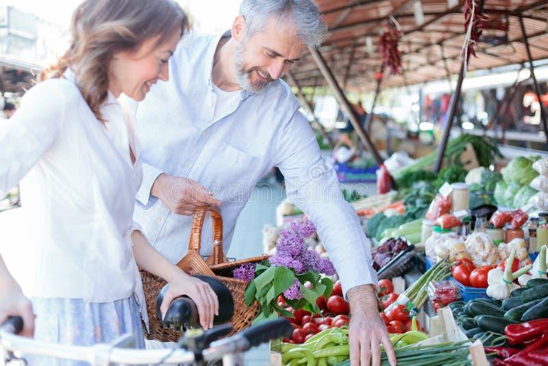 Счастливые усмехаясь покупки супруга и жены для бакалей и свежих продуктов в рынке стоковое изображение